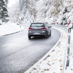 Schmitten, Germany - November 8, 2016: A driver in a Volkswagen Golf drives slowly through a dangerous curve on a road at Taunus area in Germany after a sudden start of winter in Mid-November